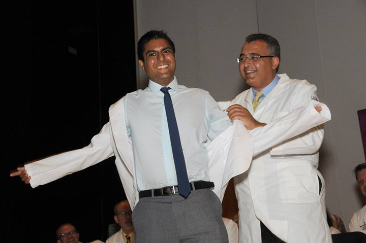 Gold 3 Docent Amgad Masoud, M.D., places the white coat on new Year 3 student, Ankit Mehta, during the School of Medicine's annual White Coat Ceremony on Aug. 10.