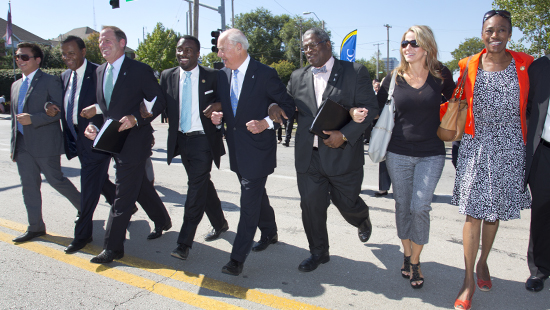 University and city leaders locked arms with community members for a ceremonial walk across Troost Avenue on Oct. 1 as part of a celebration of the construction of the first Hospital Hill student housing that is under construction.