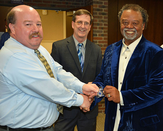 Paul Ganss, M.S., NRP, NCEE, CHSE, director of the EMS Education Program at the UMKC School of Medicine, (left) presents George McCary, III, (right) with a challenge coin medallion bearing the UMKC EMS insignia as Matthew Gratton, M.D., chair of the Department of Emergency Medicine, (middle) watches. The coin is presented in recognition of achievement. McCary is an original member of the Freedom House Ambulance Service. He received the coin after the showing of the Freedom House – Street Saviors documentary on May 21 at the School of Medicine as part of National EMS Week.