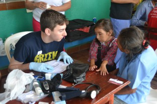 Ryan Sieli, MS 3, sees a patient at the triage station near Estelí, Nicaragua, as part of the UMKC Medical Brigade's trip to serve those in the area.