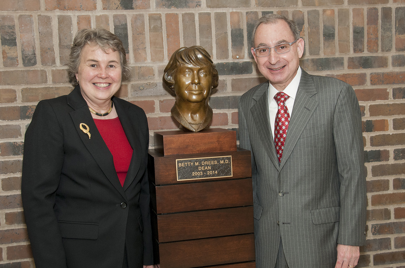 Betty M. Drees, M.D., left, and Dean Steven Kanter, M.D., pose with a bronze sculpture to commemorate her tenure as dean of the School of Medicine.